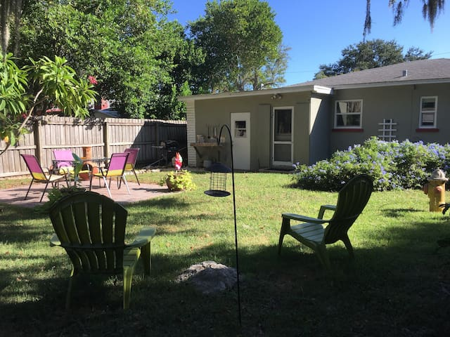 Fenced in backyard with shady seating for grilling out and a round of croquet