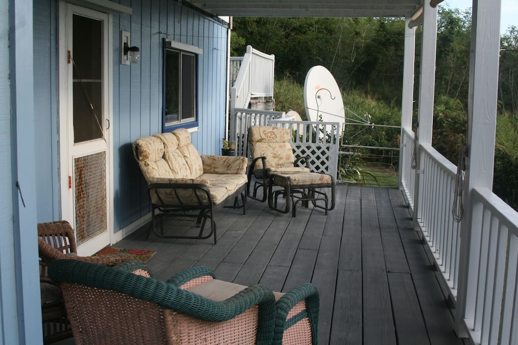 Large covered deck with gliders for relaxing.