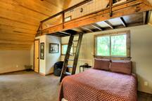 Upstairs loft area equipped with half bath, queen bed, and 2 twin loft beds.