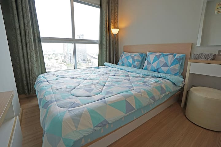 King sized bed with big window and darkening curtain.