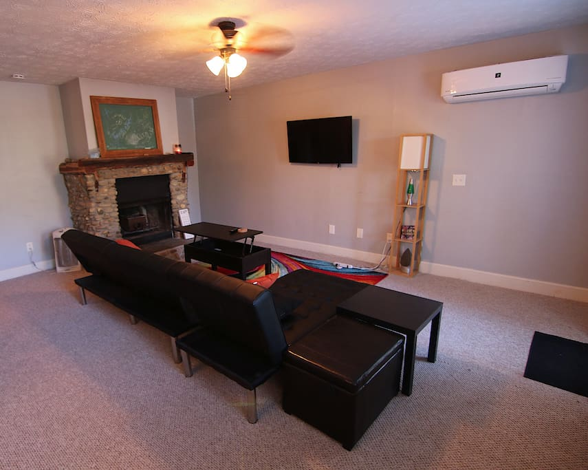 Living room has lift-top coffee table, two futon couches, flat screen smart tv equipped with WiFi.