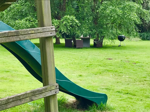 The children's play frame, little sand pit and mini climbing wall is all visible from your dining furniture and BBQ under the trees.