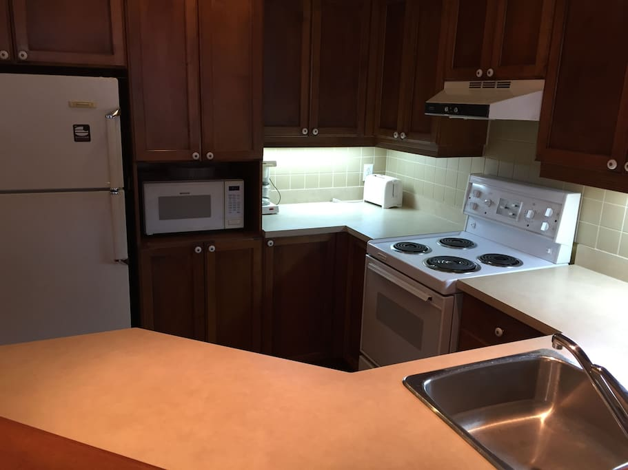 Comfortable stocked kitchen complete for pots, pans dishes, microwave kettle and more