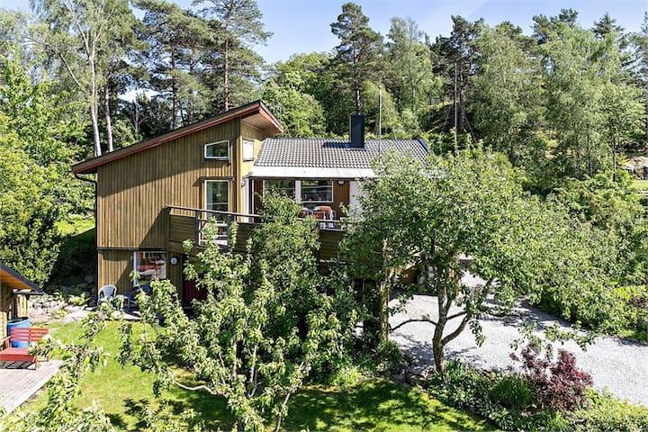 Havsnära hus med lummig trädgård och havskajaker.