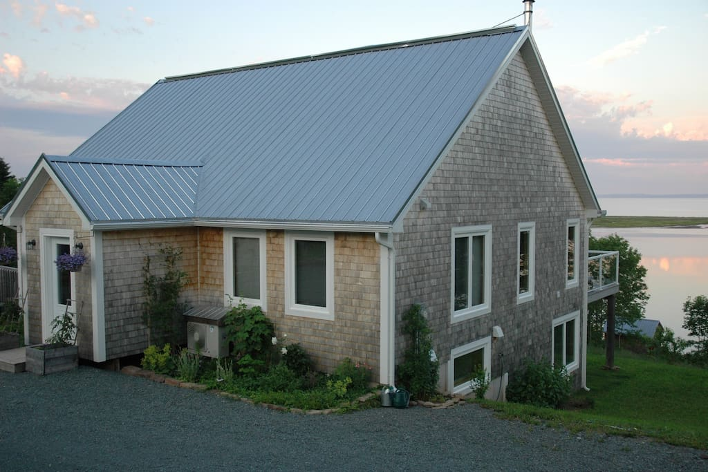 the cedar-shingled home looks out onto St. Georges Bay, and is surrounded by gardens