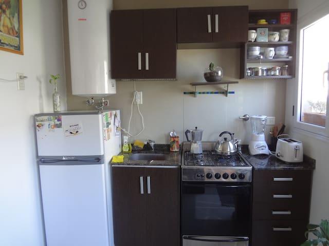 Cómoda cocina, con todo tipo de utensillo, vajilla, cacerolas, ensaladeras, licuadora, tostadora, cefetera.