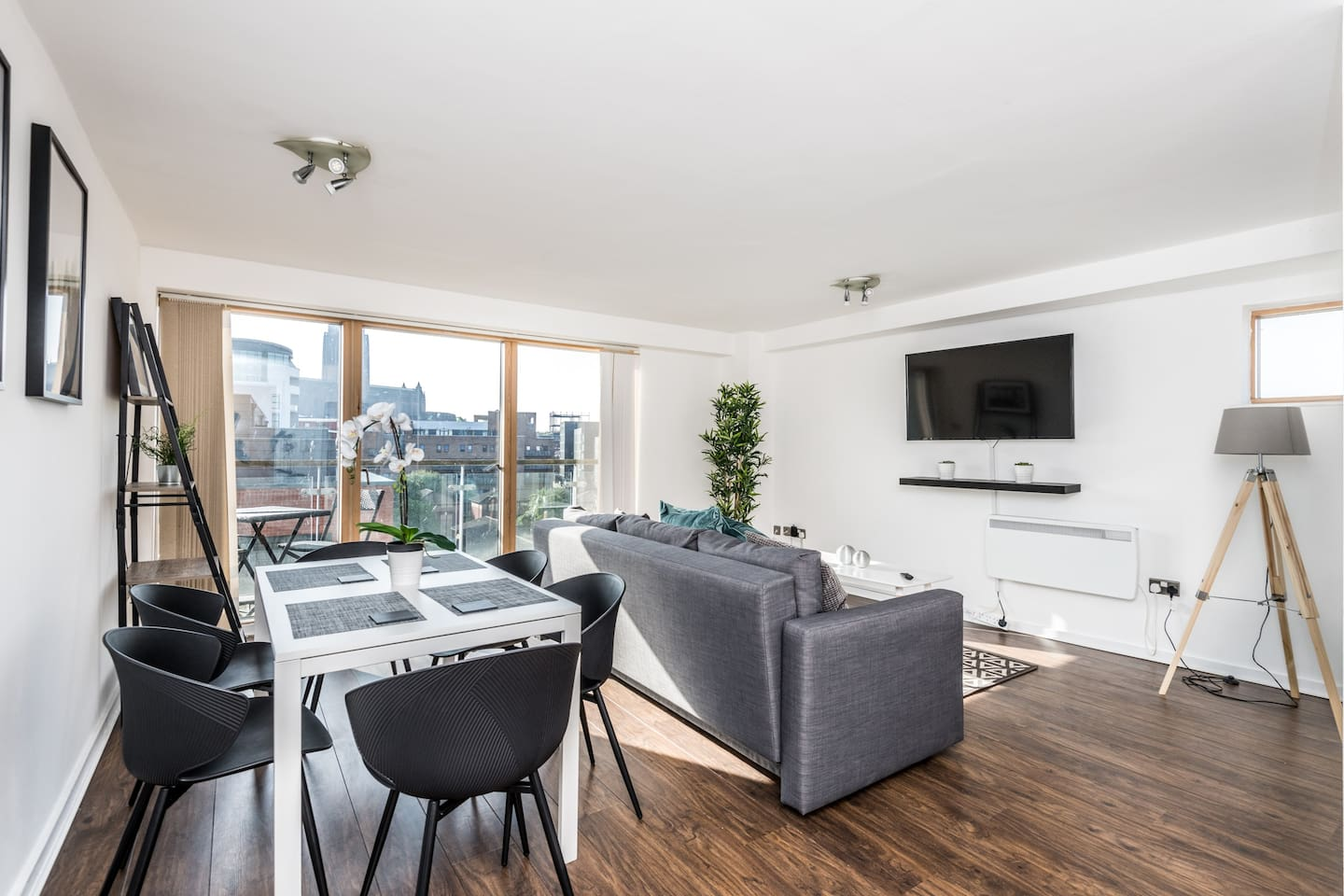 The main area of the apartment consisting of a sofa bed, smart TV, a dinning table for 6 guests and an entrance to the balcony!