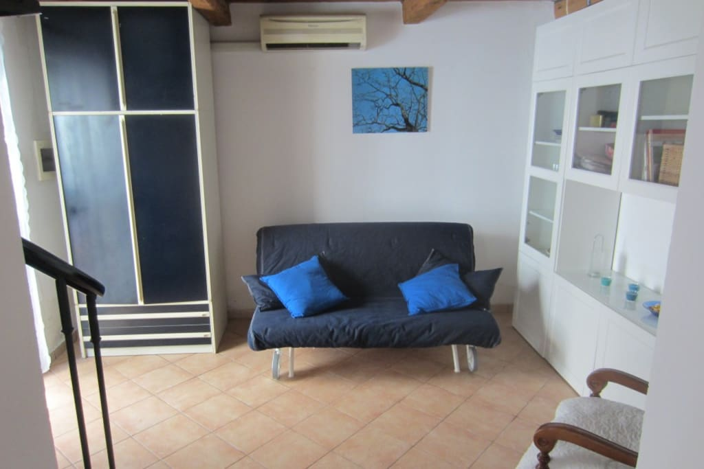 Sala con divano letto. Living room with sofa bed.