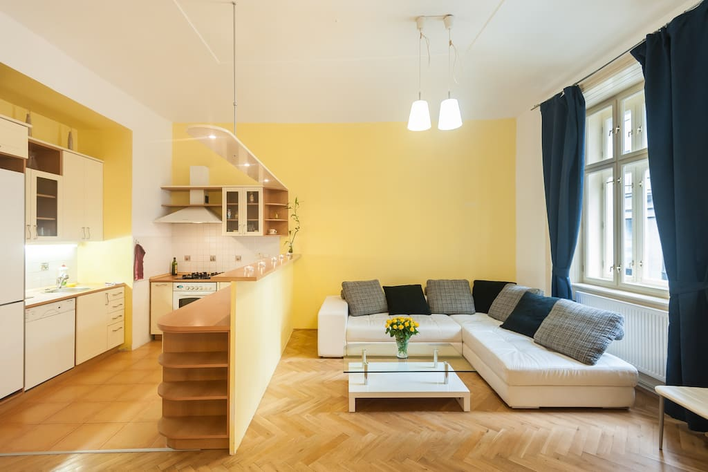 A large bright living room with 3,5 m high ceilings combined with kitchen and dining area that offers a pleasant view on typical rich European neighborhood. The comfortable sofa can be further used as a double bed.