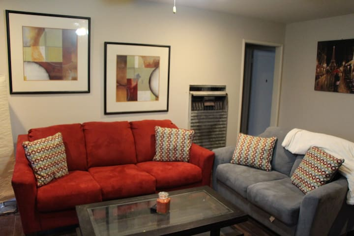 Comfortable modern couches and wooden coffee table with glass panel
