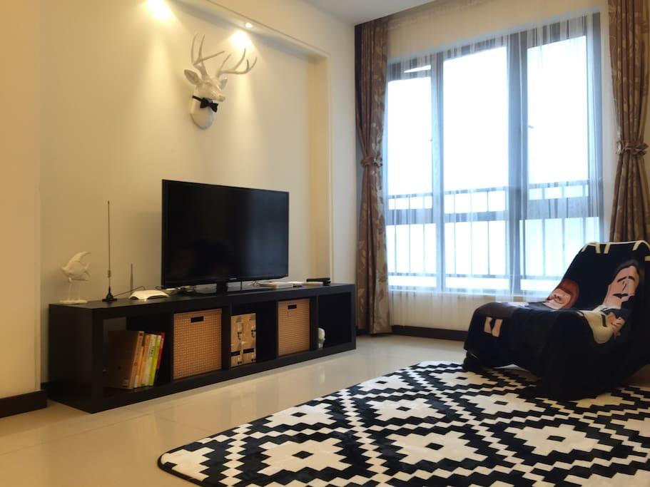 三五好友坐在客厅的地毯上,看着窗边的白色纱帘随轻风摆动,凉风拂面,享受愉快的假期,别有一番惬意