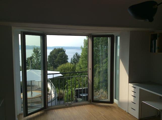 Arkitekttegnet annex/studio med fjordutsikt og sol