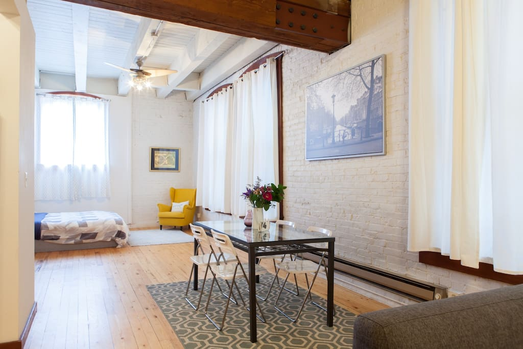 Original windows and white brick in a spacious loft featuring hardwood floors and high ceilings.