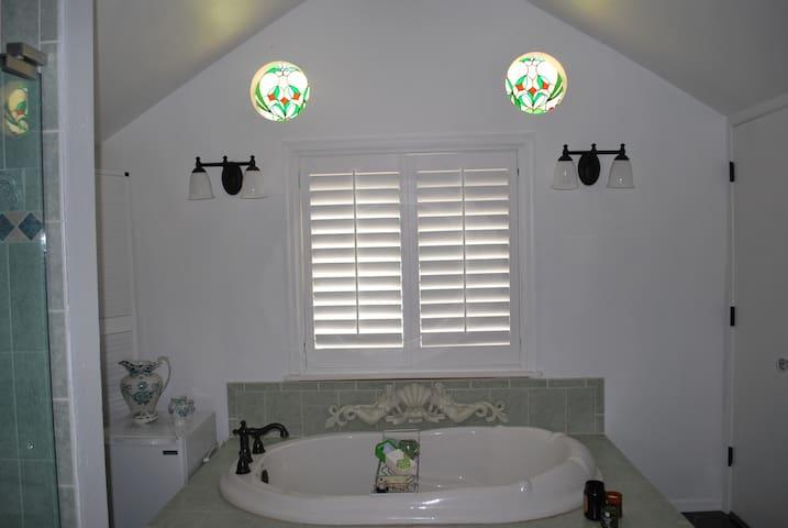 Bathroom tub and colored glass windows.