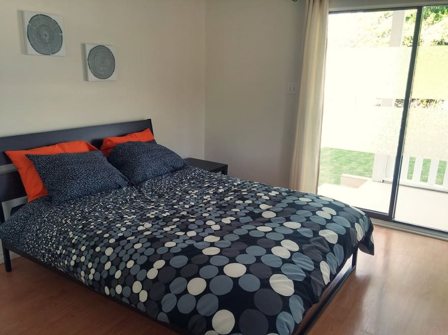 Master bedroom contains a queen bed and a sliding door onto the deck overlooking the front yard.