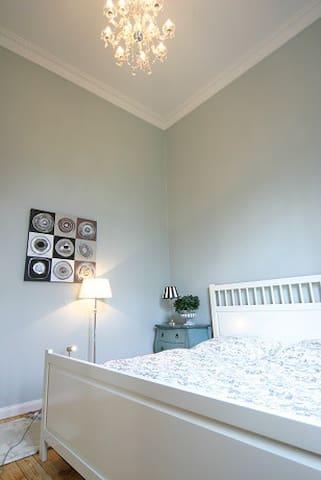 Schlafzimmer mit Doppelbett - Blick in einen großen Garten