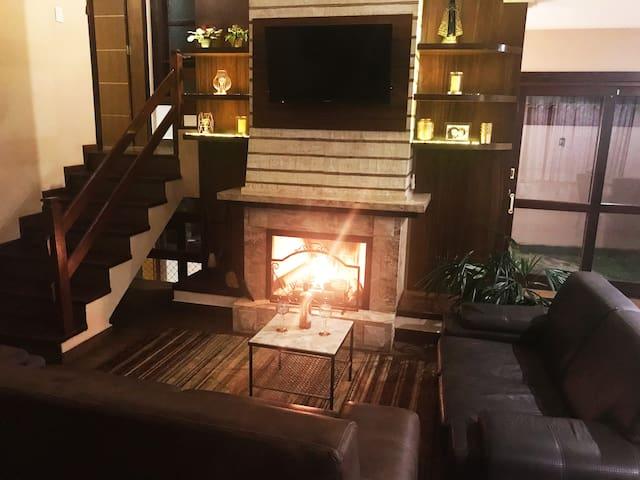 Sala de estar com lareira acessa e iluminação romântica. Ambiente ideal para uma noite de queijos e vinhos ou fondue a dois ou com amigos.