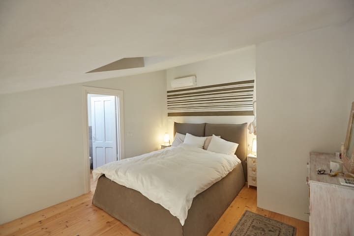 The bedroom has one comfortable bed (160x200) with a set of two duvets and four pillows. Left you see the door to the upper bathroom. Aircon is available in both rooms upstairs.