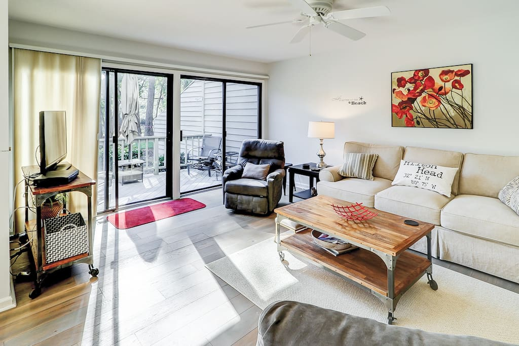 Sun-drenched living area for 7, furnished with a sofa, love seat, and armchairs. Home professionally cleaned by TurnKey's dedicated housekeeping staff.