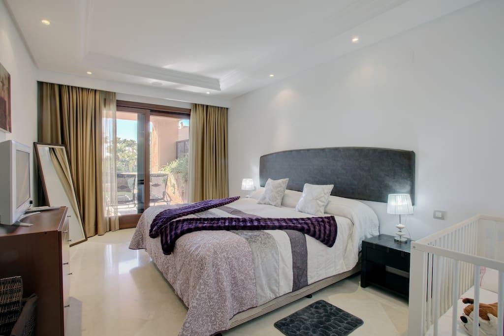 An elegantly decorated master bedroom with full-length panoramic windows leading to the terrace.