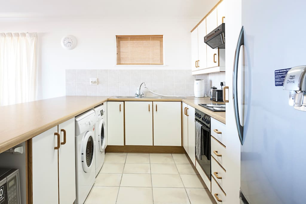 Open plan kitchen, with washing machine & dryer.