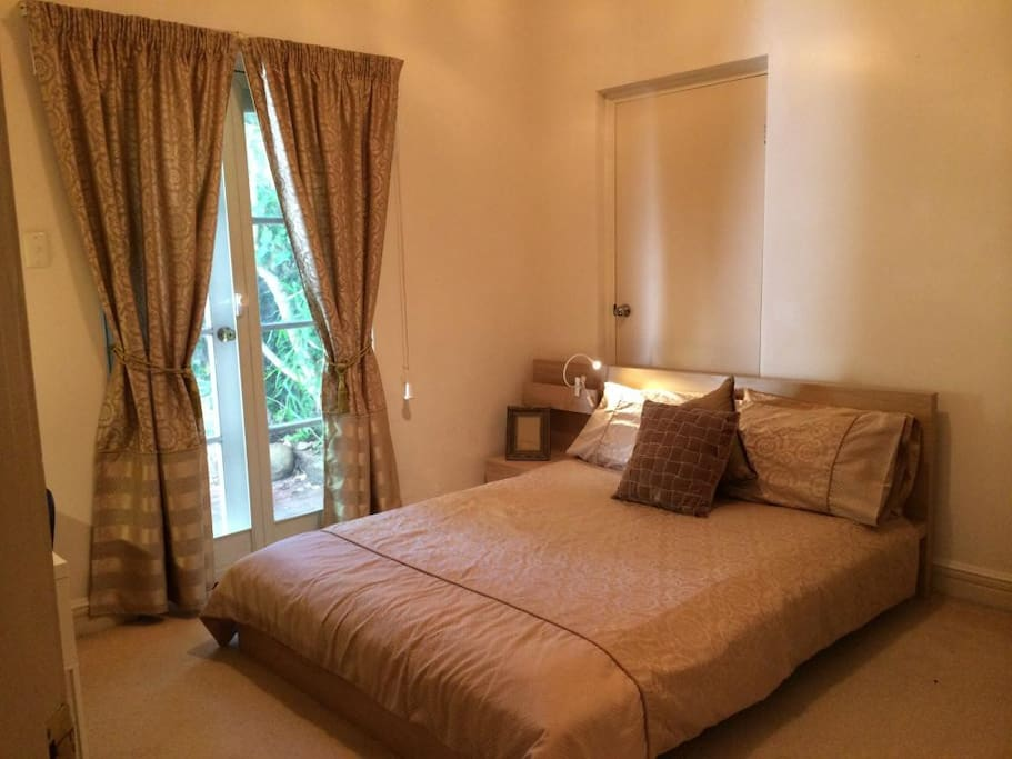 The bedroom with queen size bed and French doors opening to a private courtyard.