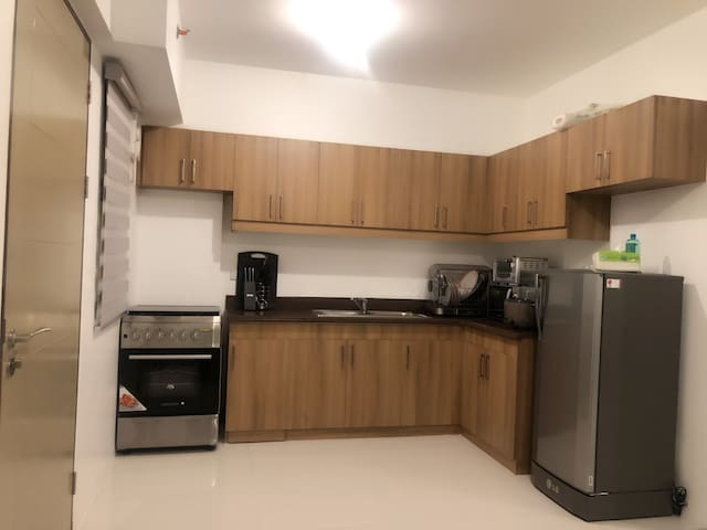 Kitchen with complete cooking utensils. With refrigerator, microwave, toaster, oven, blender and dish sterilizer.