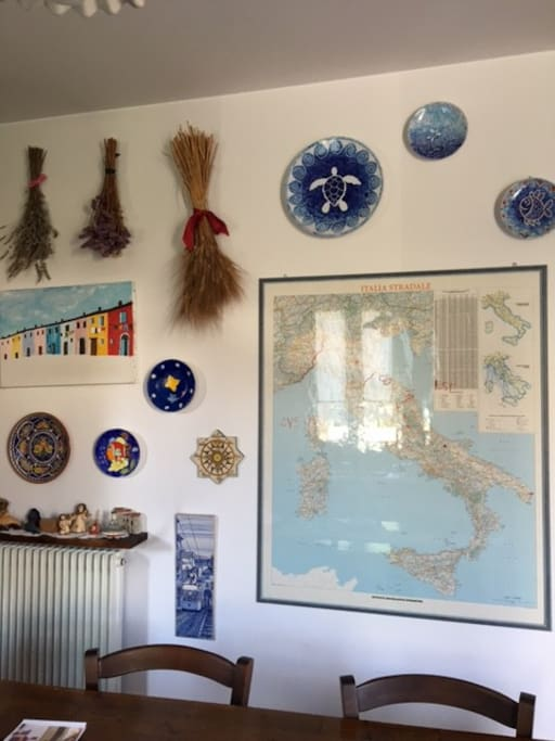 the wall with a map of Italy, some hanging dishes of Lampedusa and lavender , flowers and wheat crop in the field of my mother.