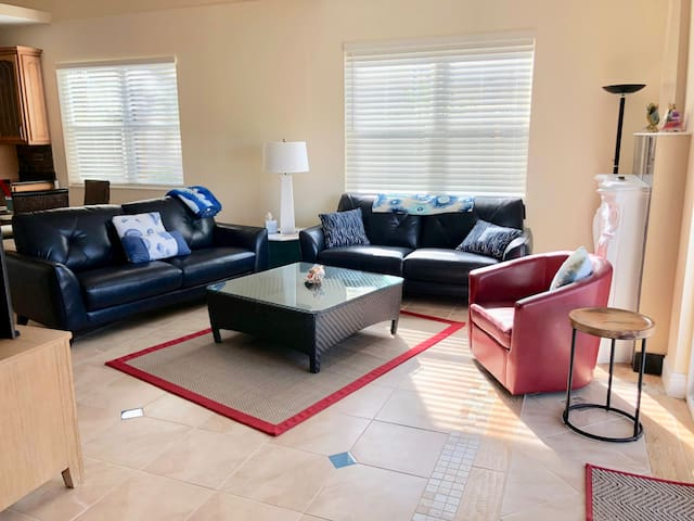 Seating in living room includes 2 leather couches and a tub chair