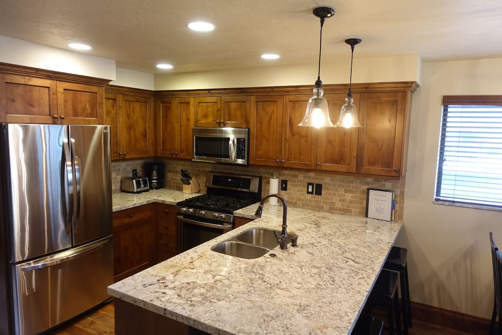 Kitchen with gas stove, granite countertops, and stainless appliances