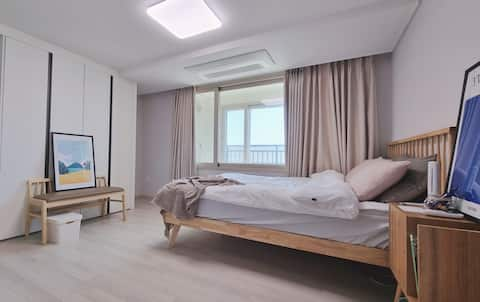 A comfy sunny room with a view of the Jeju Ocean