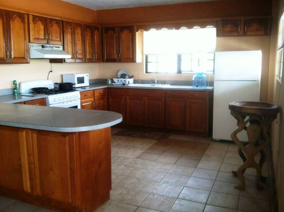 Kitchen with stove, toaster oven, microwave and fridge.