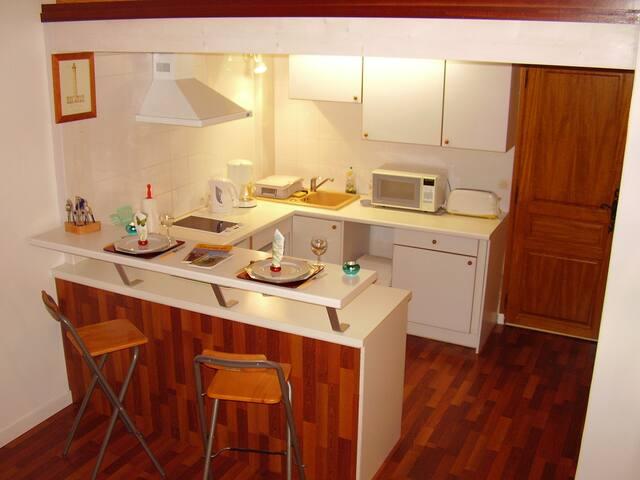 Le coin cuisine situé dans la pièce à vivre. Au font, la porte de la chambre.