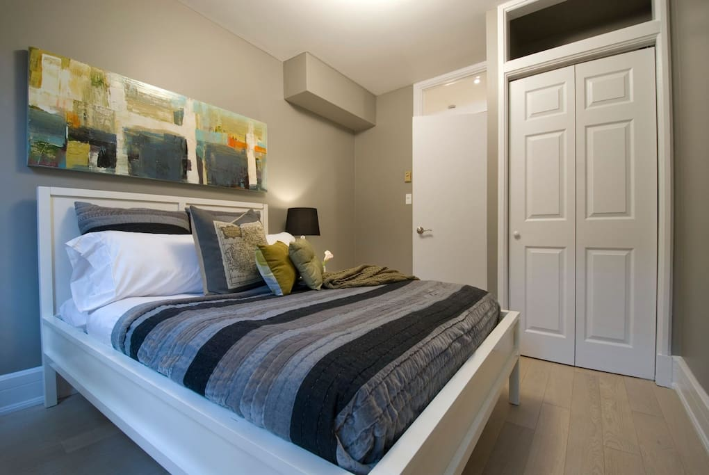 The comfortable main floor bedroom with a closet, backs onto the quiet, private garden/ deck area.