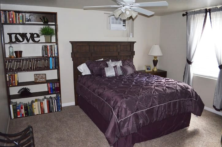Master bedroom with queen bed , ceiling fan, recliner, and large window