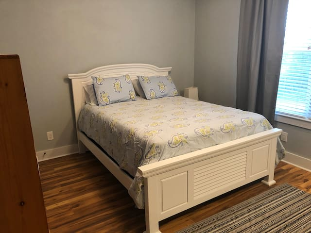 Queen bed with kitchenette. Large picture window has bay views through the pine trees.