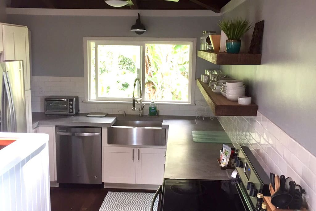 Newly updated Farmhouse style kitchen with stainless steal appliances & custom concrete countertops.  Window Looks out to tropical plants.