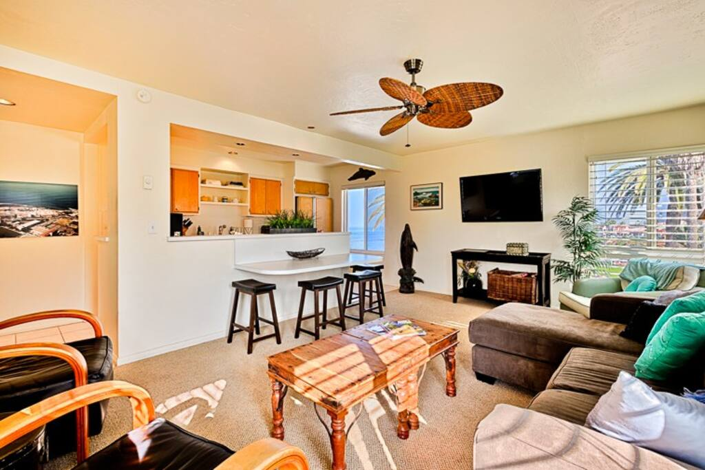 Ocean view living room is open to the kitchen, with a dining table for 4 people.
