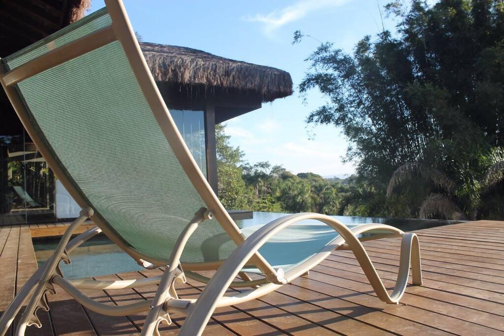 Área comum com piscina, deck, churrasqueira, sala de estar e banheiros.