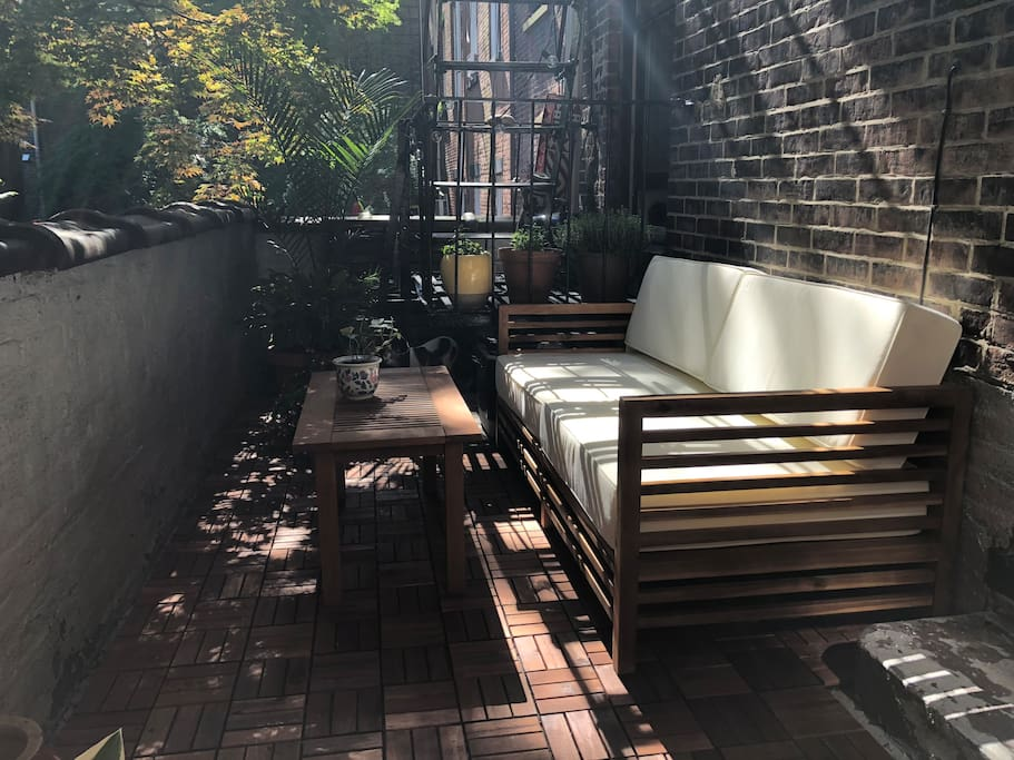 Recently refurbished patio with a loveseat and another bench. It's a beautiful place to enjoy your morning coffee or just relish being at home outside in Brooklyn Heights!