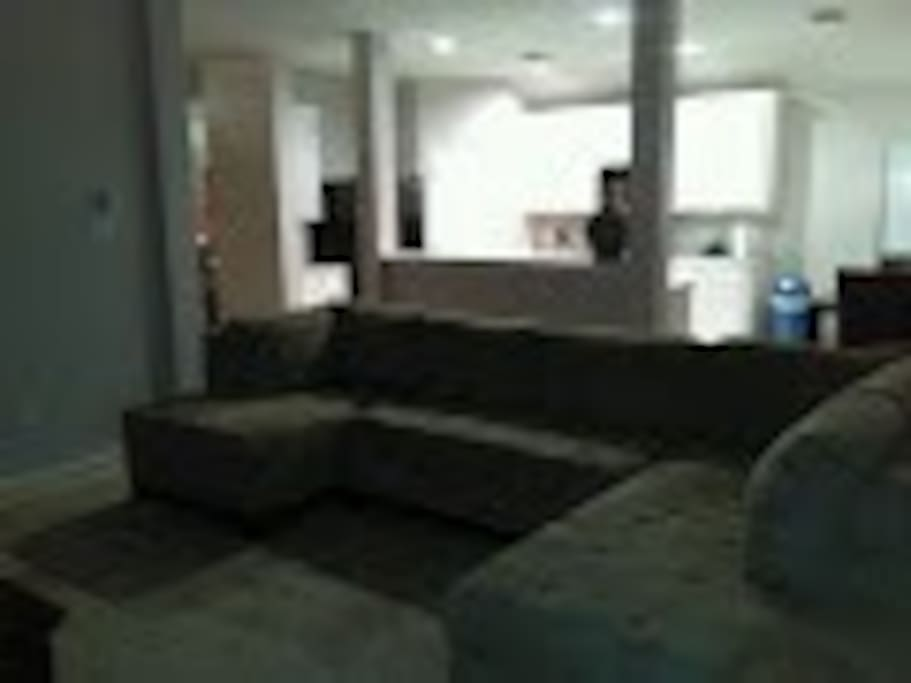 Front view of sofa with open kitchen in background for television viewing from afar.