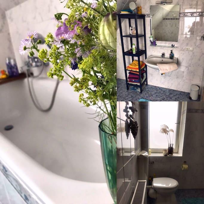 Das Badezimmer mit Wanne, Waschbecken, Handtüchern, Föhn, Regal und Toilette
