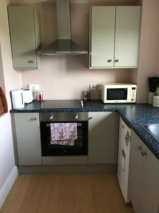 Small kitchen with oven/hob/microwave/cooking saucepans and utensils