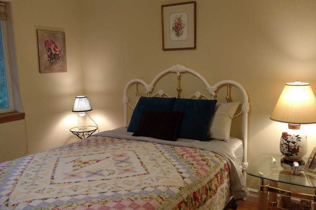 Rose Room queen size bed with full closet, private bathroom next door, view of the forest