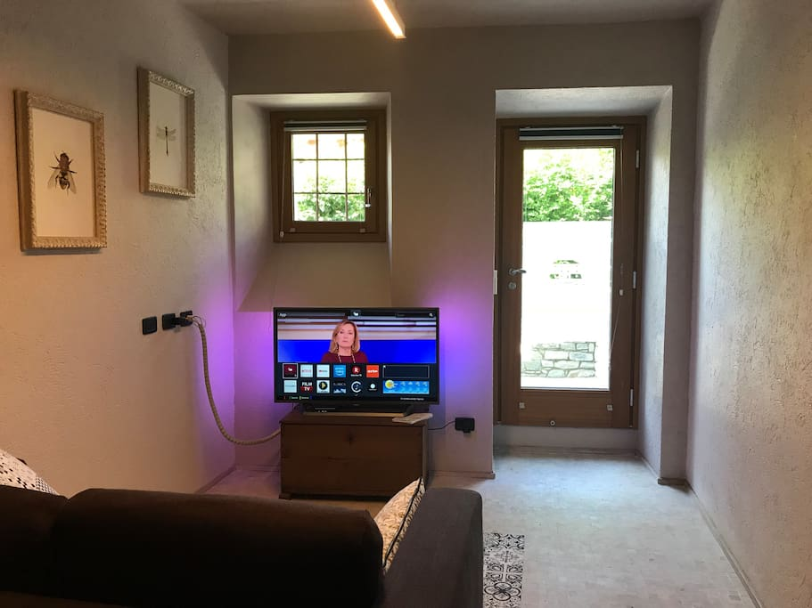 zona soggiorno con Smart TV e divanoletto