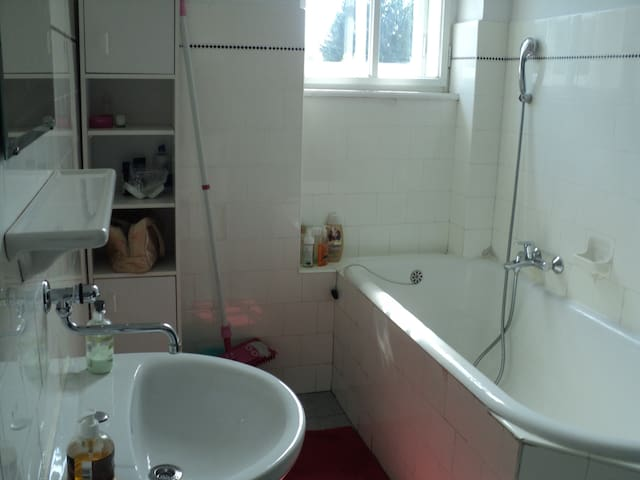 The bathtub doesn't have a curtain, but there is a mop beside that you can use to clean, if the floor gets wet.