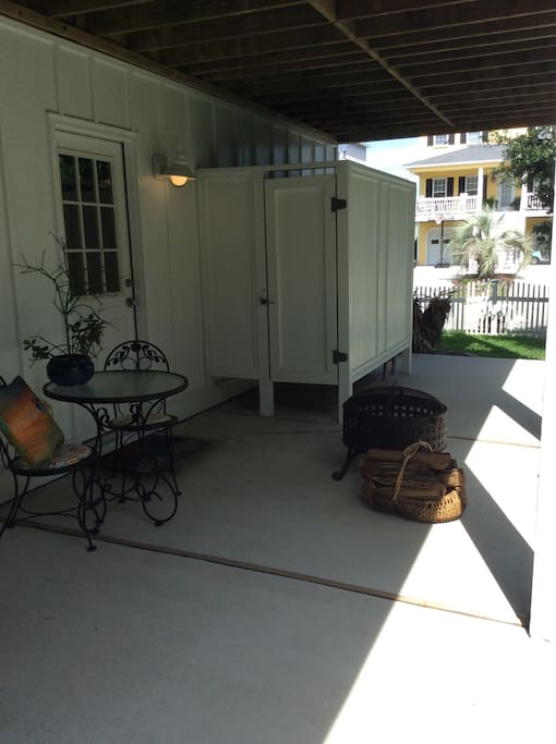 Backyard patio with seating, fire pit, grill, and a shared outdoor shower.