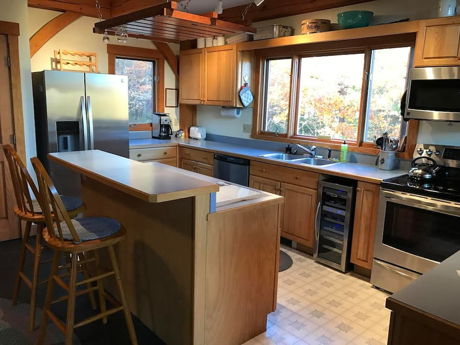 Inviting kitchen with prep island, seating and wine refrigerator