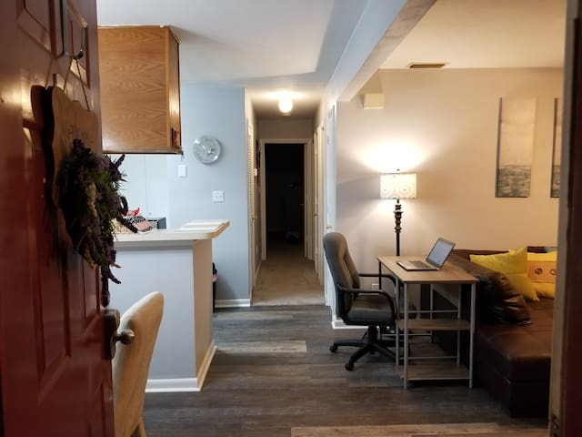 Entrance from front door.  View of living room (on the right) with office desk and chair (laptop is for display only).  Dining room and kitchen on the left.  Hallway to en suites straight ahead.