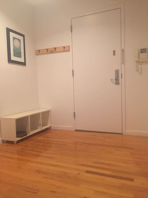 private entrance into foyer with coat hooks and bench for shoes, slippers and extra space for luggage